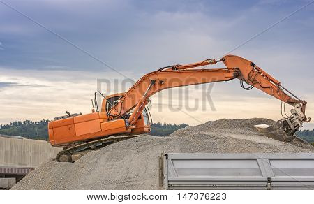 Excavator  - Orange excavator climbed on a ballast pile loading material in a trailer.