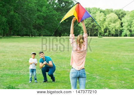 Family Flying The Colorful Kite Together In The Park