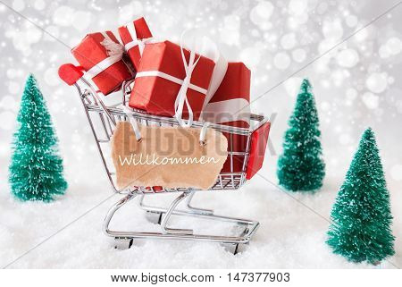 Trollye With Christmas Presents Or Gifts. Snowy Scenery With Snow And Trees. Sparkling Bokeh Effect. Label With German Text Willkommen Means Welcome