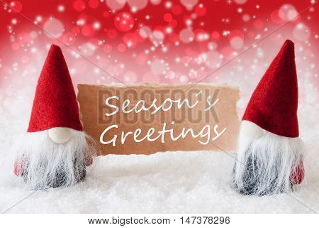 Christmas Greeting Card With Two Red Gnomes. Sparkling Bokeh And Christmassy Background With Snow. English Text Seasons Greetings