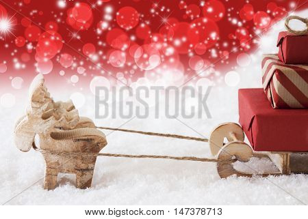 Moose Is Drawing A Sled With Red Gifts Or Presents In Snow. Christmas Card For Seasons Greetings. Copy Space For Advertisement. Red Christmassy Background With Bokeh Effect.