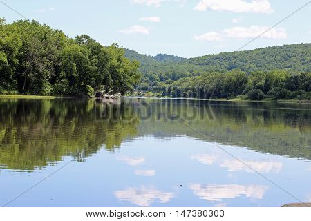 A calm view of the Susquehanna river with a downed tree and clouds in the water.