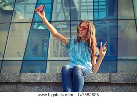 Close-up of pretty girl taking selfie in the downtown on a gorgeous summer day