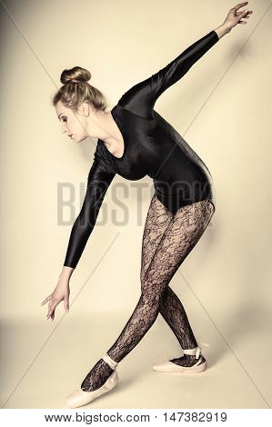 Graceful beautiful woman ballet dancer full length studio shot gray background