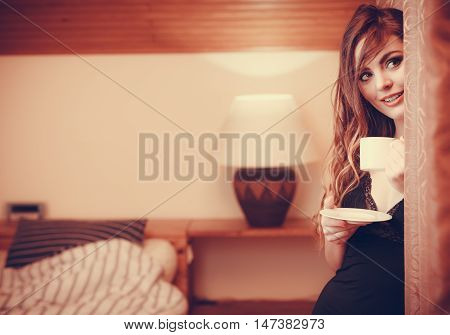 Sensual seductive woman in lingerie drinking cup of coffee by curtain at home. Young girl with hot energizing beverage stay awake. Caffeine energy. Instagram filter.