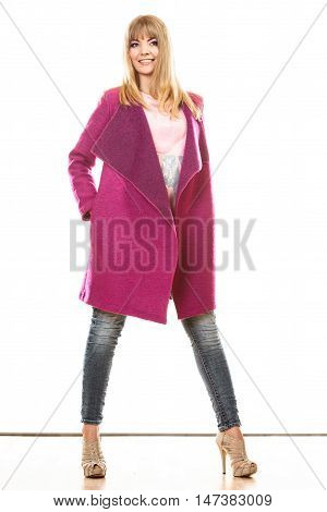 Fashion. Young blonde fashionable woman in vivid color pink coat. Female model posing isolated on white background