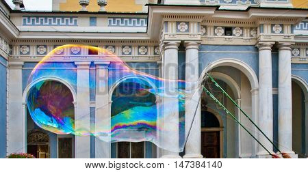 big soap bubble with a thousand colored reflections created by a juggler to make children happy on the Bressanone cathedral background
