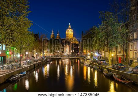 St.Nicolas church and canals at night in Amsterdam Netherlands. Nightlife in Amsterdam Netherlands.
