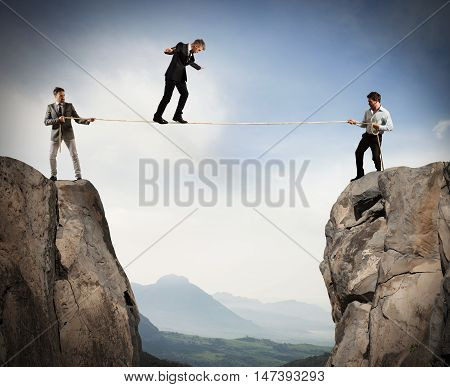 Business people holding a rope while a man balanced walking