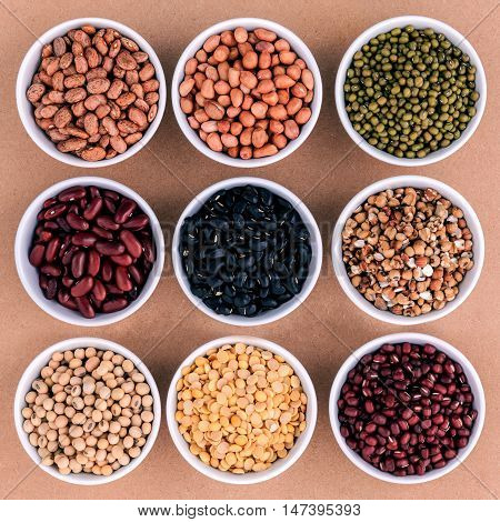 Mixed Beans And Lentils In The White Bowl  On Brown Background. Mung Bean, Groundnut, Soybean, Red K