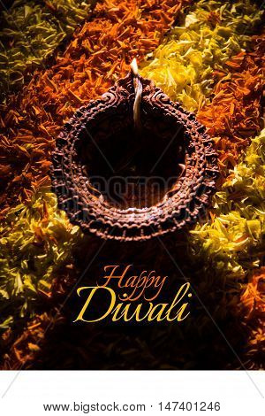 happy diwali greeting card made using a traditional Indian earthen lamp placed over marigold petal's rangoli, close up and selective focus