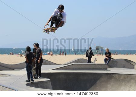 Venice Beach, California, 9/10/16--Skateboarder Steve Martinez launches high in the air at Venice Beach Skate Park, with the sand and blue Pacific in background. Extreme skateboarding started here in Venice Beach.
