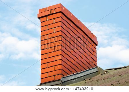 Brick chimney on roof of residential house on sunny day