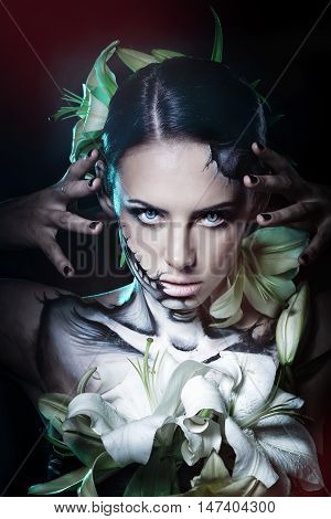Young attractive girl with creative make-up for Halloween. Close-up portrait. Mysterious and frightening image of lilies. Witchcraft.