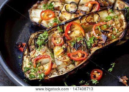 Stuffed roasted eggplant with garlic and chili, in rustic black dish.