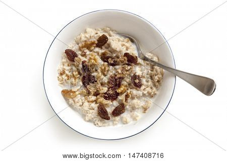 Bowl of oatmeal with raisins, walnuts and brown sugar.  Top view, isolated on white.