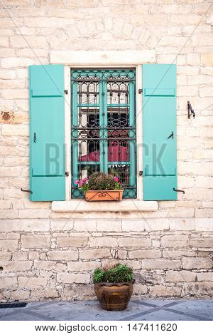 Cute window with blue shutters and flowers Cyprus