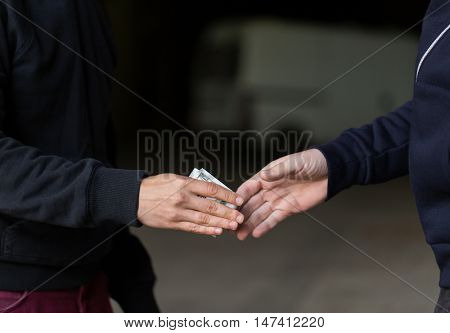 drug trafficking, crime, addiction and sale concept - close up of addict paying money to drug dealer on street
