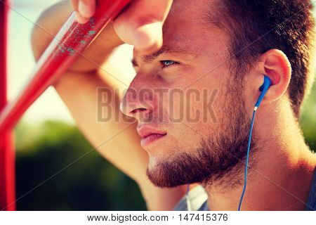 fitness, sport, training and lifestyle concept - young man with earphones listening to music and exercising on horizontal bar outdoors