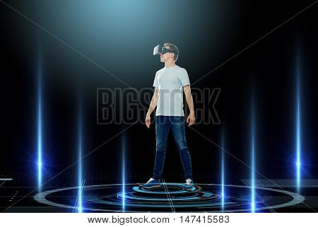 3d technology, gaming, augmented reality, cyberspace and people concept - happy young man in virtual reality headset or 3d glasses with laser lights over black background