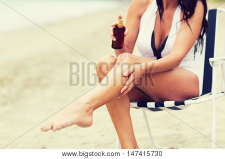 summer, travel, body care and people concept - close up of young woman in swimsuit sunbathing on folding chair and spraying sunscreen oil to her skin