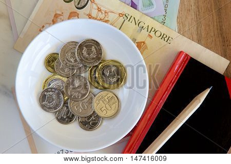 A white dish of Singaporean coins and a notebook and pencil with a background of notes.