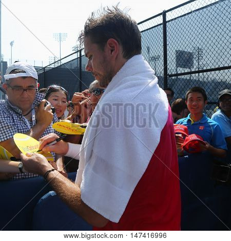 NEW YORK - SEPTEMBER 10, 2016: Grand Slam champion Stanislas Wawrinka of Switzerland signs autographs after practice for US Open 2016 at Billie Jean King National Tennis Center