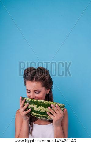 Picture of happy young woman holding a big slice watermelon in the studio.
