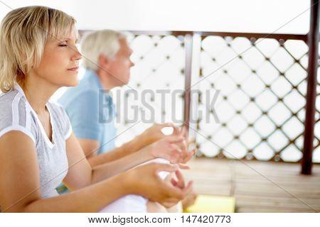 Woman sitting meditating on veranda with her husband