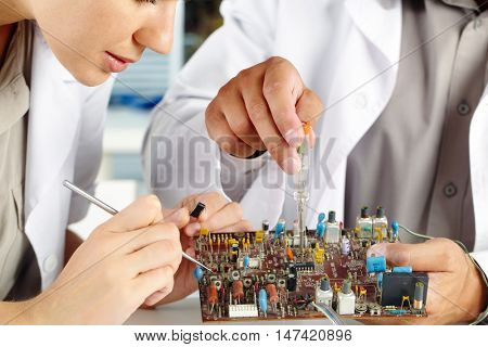 Female technician working with transistor