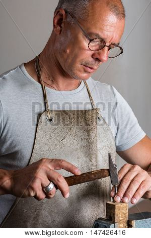 Goldsmith Shaping Thin Silver Pieces With Hammer