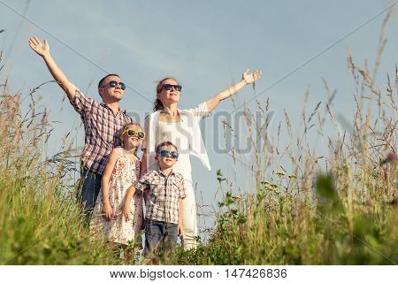 Happy family walking on the field at the day time. Family having fun on the park. Concept of friendly family and of summer vacation.