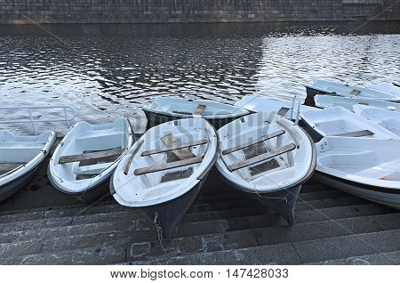 Pleasure boats against the backdrop of the city canal. Empty boats in a row. Nobody around. The end of the summer season. Rowboats at a boat station.
