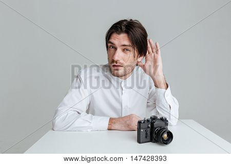 Young bristled brunette man which overhears conversation while sitting at the table isolated on the gray background