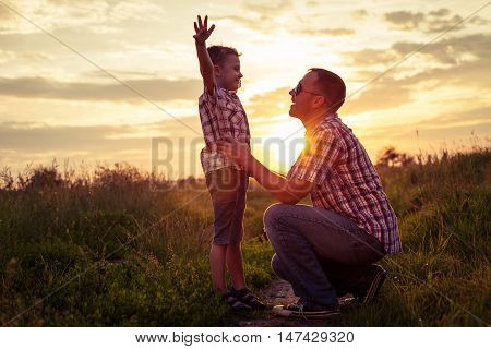 Father and son playing at the park at the sunset time.Family having fun on the field. Concept of friendly family and of summer vacation.
