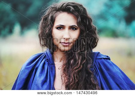 Young beautiful curly-haired witch witch in blue raincoat