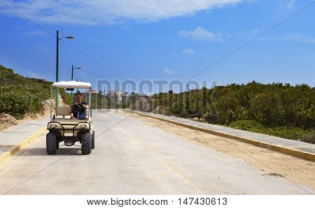 Man by golf car on the seashore. Mexico. Women Island.