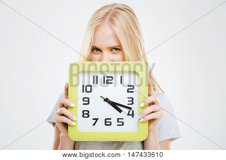 Cute smiling blonde woman peeking out of wall clock isolated on a white background