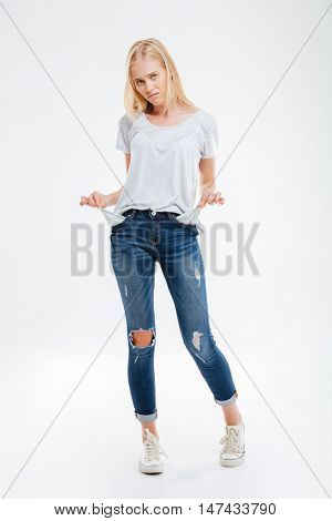 Depressed young woman showing empty pockets isolated on a white background