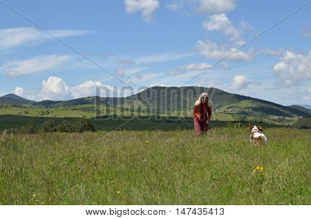 Joyful blonde woman in red plying with her dog (Cavalier King Charles Spaniel) on a meadow and wonderful landscape