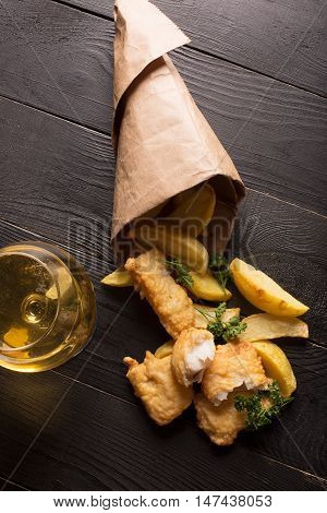 Traditional British fish and chips on the black background with glass of beer. Top view