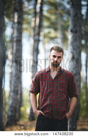 Handsome fit man posing outdoors in forest wearing checked shirt
