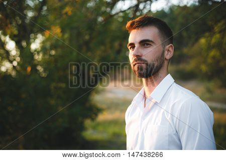 Handsome casual bearded man in white t-shirt outdoors