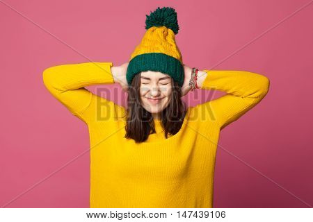 Young teenager girl closing ears with her hands isolated. Hipster stress. Young girl wearing yellow bright clothes covering ears