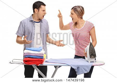 Young couple arguing behind an ironing board isolated on white background
