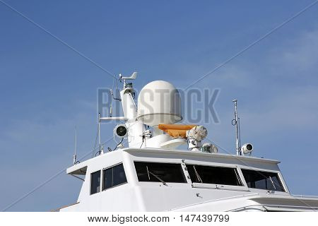 Ships antenna and navigation system in a clear blue sky.