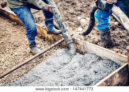Industrial Workers Handling Massive Cement Pump Tube And Pouring Fresh Concrete On Reinforced Bars A