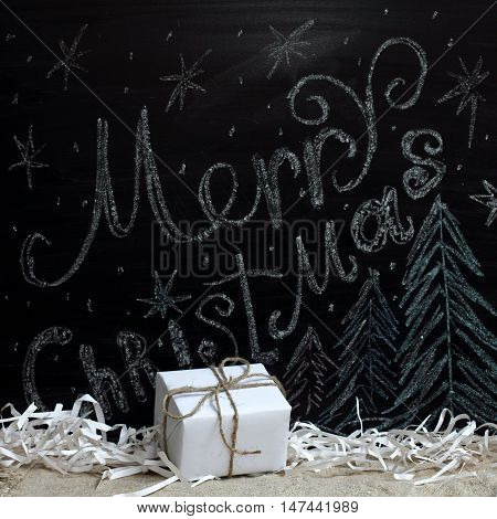 holiday gift on the background of congratulations drawn in chalk on a blackboard / standby Merry Christmas