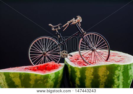Sur. Vintage bicycle standing on top of a large cut in half scarlet ripe watermelon
