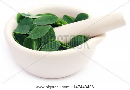 Edible moringa leaves in a mortar with pestle over white background